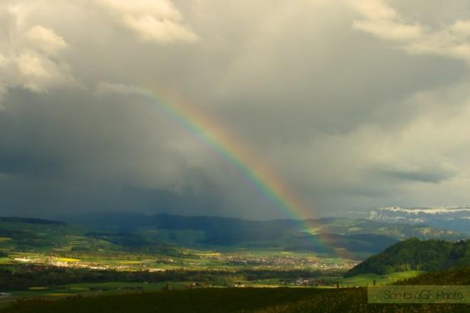 Arcoíris en berna campos verdes montañas cielo de tormenta fotografía de paisajes