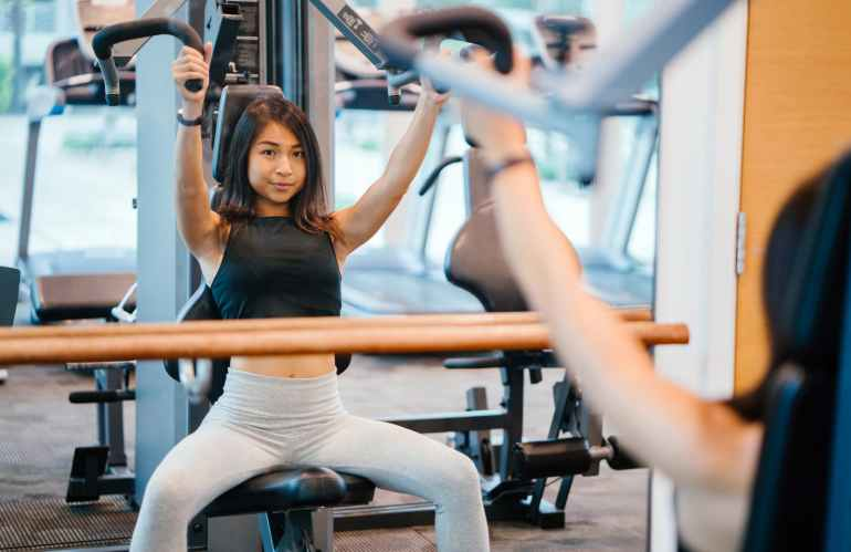 woman in black sleeveless crop top and white leggings using a butterfly machine in front of a mirror