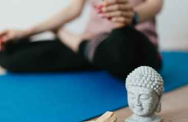 anonymous young woman sitting on floor in ardha padmasana position near esoteric objects used for meditation