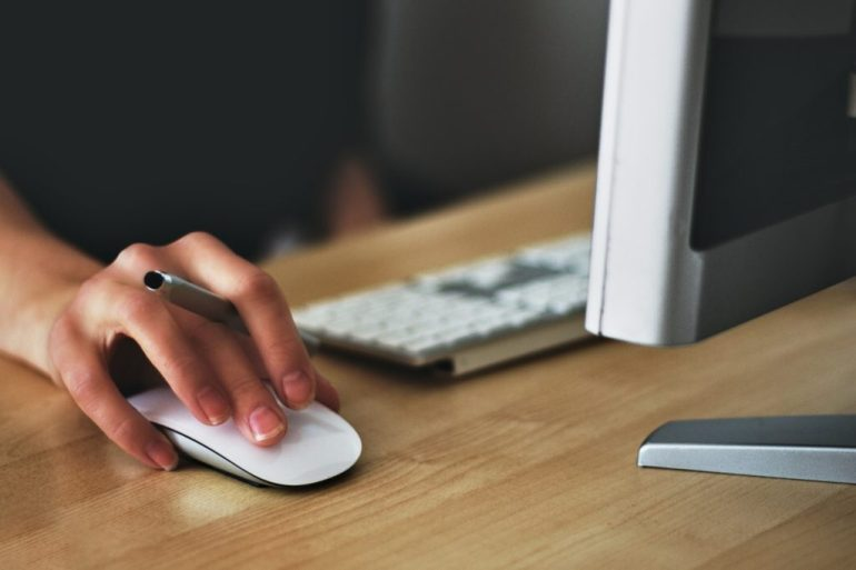 Woman working on computer holding a mouse
