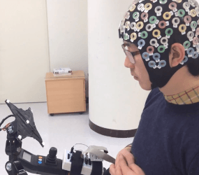 Using an electroencephalogram (EEG) cap, the system allows users to move forwards, turn left and right, sit and stand simply by staring at one of five flickering light emitting diodes (LEDs)