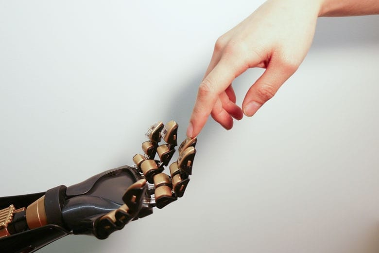 Stanford chemical engineering Professor Zhenan Bao and her team have created a skin-like material that can tell the difference between a soft touch and a firm handshake. The device on the golden ?fingertip? is the skin-like sensor developed by Stanford engineers. (Bao Lab)