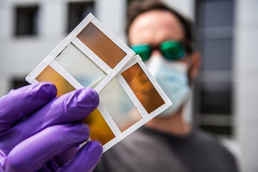 NREL researcher Lance Wheeler holds samples of perovskite-based window technology. Photo by Dennis Schroeder, NREL
