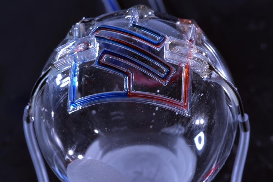 Researchers at the University of Minnesota are the first to 3D print microfluidic channels on a curved surface, providing the initial step for someday printing them directly on the skin for real-time sensing of bodily fluids. Credit: McAlpine Group, University of Minnesota