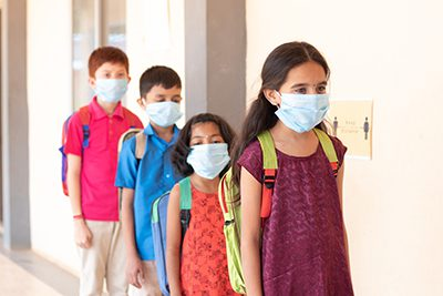 School childrens standing line in front of class while maintaining social distance outside classroom with medical mask wearing - concept of covid-19 or coronavirus safety measures at school via ACS