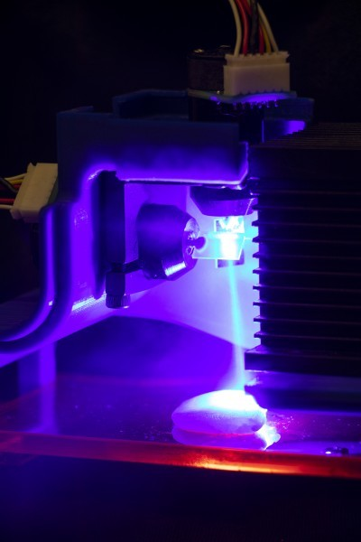 Jonathan Blutinger/Columbia Engineering Chicken being cooked by a blue laser. Light is being directed by two software-controlled mirror galvanometers.