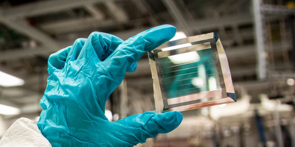 Xinjing Huang, a doctoral student in Forrest's lab, holds a solar cell module with 40% transparency, based on the formula with an estimated 30-year lifetime. Photo: Robert Coelius/Michigan Engineering.