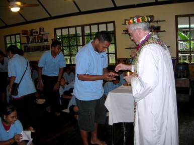 Fr. Ciancimino gives Communion to students at Yap Catholic High School.