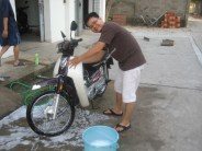 A scholastic washes his motorbike.