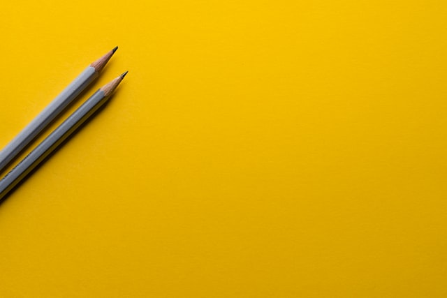 Two pencils on yellow background