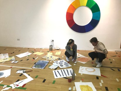 Two people crouch on the floor of a gallery space looking at artwork. There is a circular rainbow on the white wall behind them.
