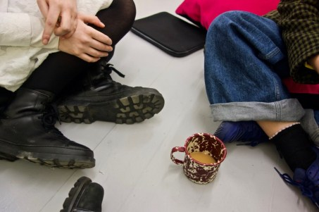 A close-up of three people sitting cross-legged on the floor. A mug of tea sits between them.