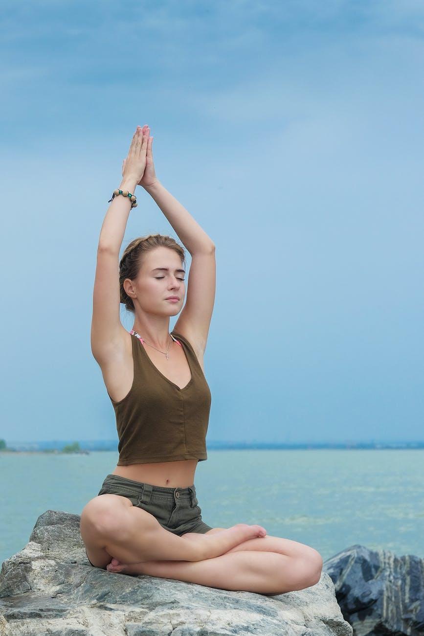 woman doing yoga on boulder near sea