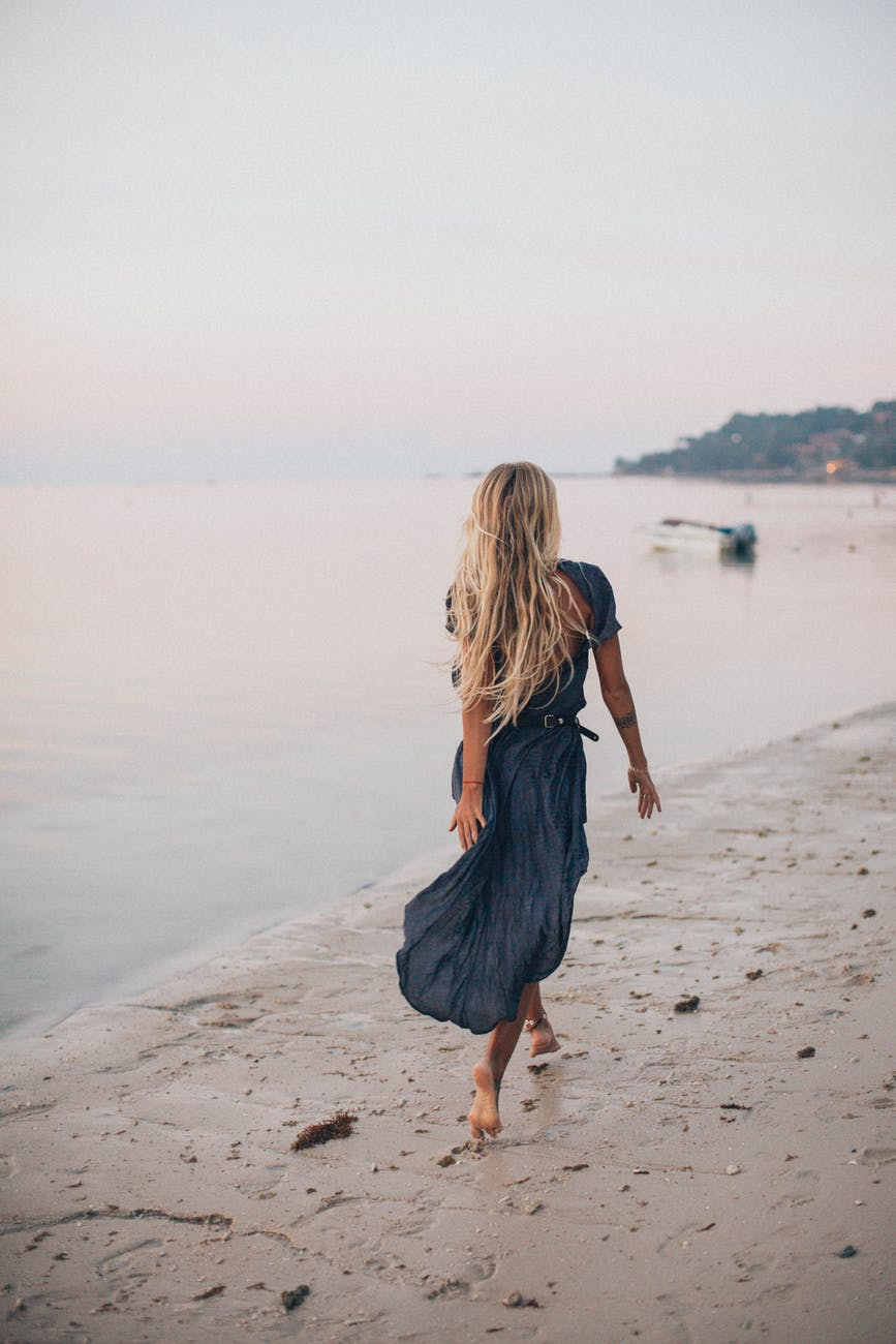 back view of a woman walking on the seashore
