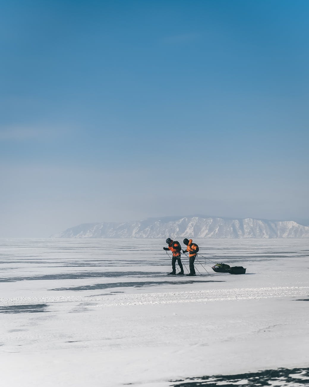 unrecognizable backpackers skiing on frozen lake in winter