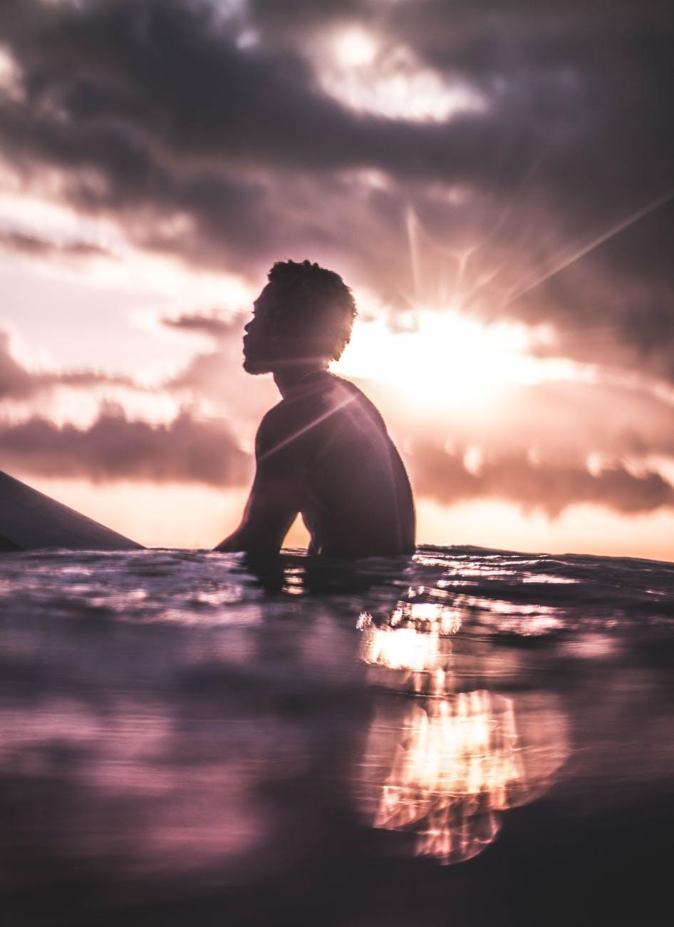 unrecognizable black man relaxing in sea water at sundown