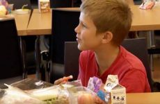 Young student eating at the library.