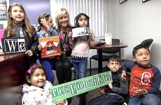 Students holding character vocabulary signs