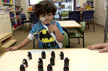 Young student trying to figure out a penguin game at the Lucile Packard Children's Hospital Stanford.