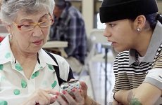 Student helping senior community member with technology.