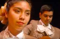 mariachi female student dressed in costume, playing in band.