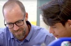 Teacher helping refugee student.