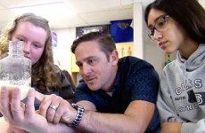 Teacher and students looking at science experiment