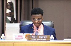 tyler okeke sitting at school board meeting