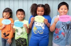 young students holding up social emotional learning cards