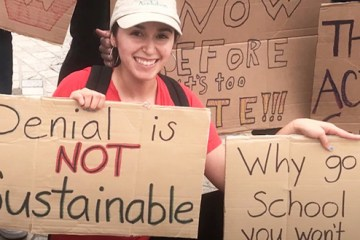 student holding up a sign for climate change