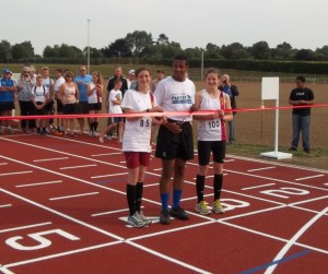 On the run: three young athletes cut the tape at the official opening of Woodcote track
