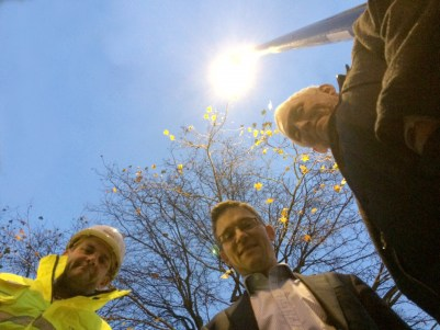 Councillor Stuart King, centre, 'celebrates' the conclusion of Sjkanska's street light installation. Only four months late. Note how they've posed under a streetlight that's positioned close to a tree canopy