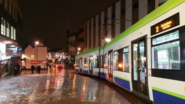 A Croydon tram navigates the slush last night - but delayed by inconsiderate drivers blocking junctions
