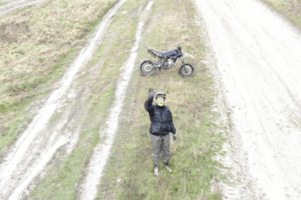 A dismounted motorcyclist waves at the camera above him. His motorcycle is behind him, right on the edge of a track.