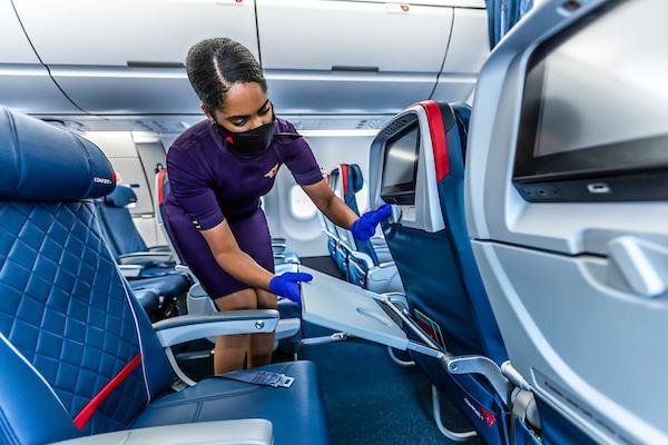 Flight attendant cleaning on board (Source: Delta)