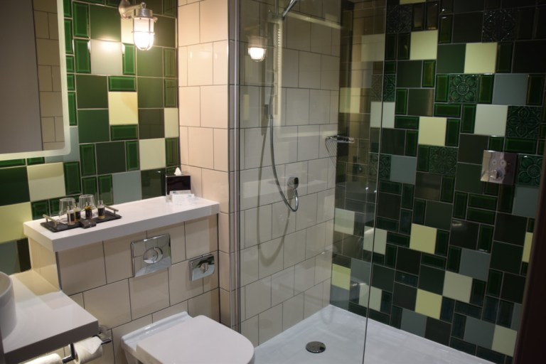 De groene tegels geven een mooi accent in de badkamer
