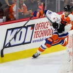 Center Scott Eansor (#36) of the New York Islanders and Left Wing Oskar Lindblom (#54) of the Philadelphia Flyers pursue the puck behind the net