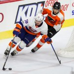 Left Wing Oskar Lindblom (#54) of the Philadelphia Flyers chases Defenseman Mitchell Vande Sompel (#58) of the New York Islanders from behind the net