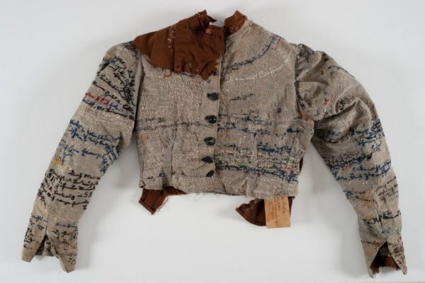 Photograph of a handmade jacket with embroidered text of many colors all over the fabric. The jacket is old, gray in color, and the sleeves are uneven.