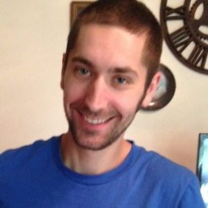 Image of a man in a blue shirt smiling at the camera.