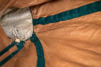 The brown cotton underlining of this bodice provides a beautiful contrast to the green silk taffeta of the outer fabric. The taffeta and cotton layers were cut and sewed as one piece. When the seams were opened, the edge of the taffeta was turned under and finished.