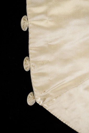 The embroidery on the buttons is done before cutting the satin. The circles were then cut out and used to cover the buttons.