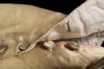 When the buttons at the knee of the breeches are unbuttoned, the pink selvedge edge of the satin is visible. The inclusion of the selvedge indicates that the tailor used the entire width of fabric. It also makes the edge easier to finish since the selvedge will not unravel.