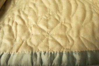 Interior of quilted petticoat showing hem facing and wool lining.