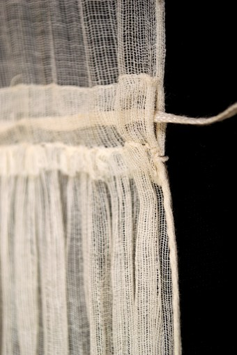 The back of the dress fastens with a drawstring at the waist. The fabric is so sheer that the string can be seen right through the casing. The edge of the center back opening is finished with the most delicate rolled hem.