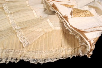 Around 1880, skirts were relatively slim down the legs but finished in a wide, sweeping train. To keep the train from folding in on itself and from wearing out on the floor, the floorside of the skirt was finished with rows and rows of ruffles. The term in French for the bottom ruffle is balayeuse, which means sweeper. This cotton ruffle was easily replaced once it wore out.