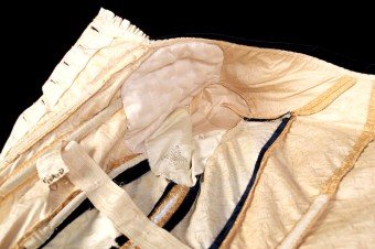 One of the benefits of custom made clothing is that it can compensate for perceived figure flaws. A peak inside this bodice reveals that the bust has been generously enhanced with padding.