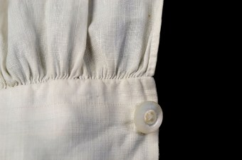 Near the edge of the cuff, a single thread has been drawn from the linen fabric to mark a straight line and to ensure that the pieces are square to the grain.