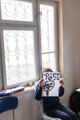 A student describes her drawing during an art therapy session in Kahramanmaras, Turkey, by Mieke Strand