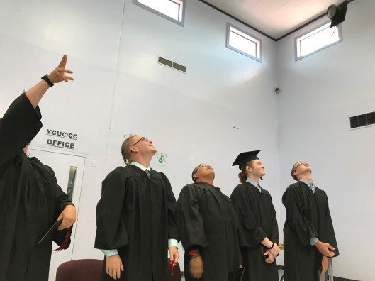 Trask River High School graduates throw their caps into the air at the end of the June 21 graduation ceremony at Tillamook Youth Correctional Facility.
